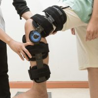 Therapist fitting a knee brace to patient leg